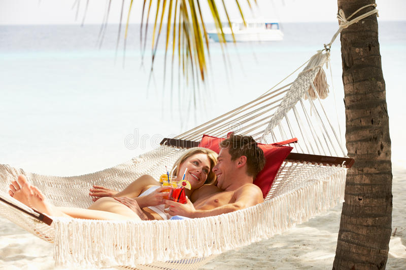 Romantic Couple Relaxing In Beach Hammock. Smiling stock image