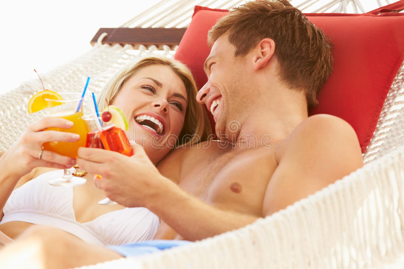 Romantic Couple Relaxing In Beach Hammock. Smiling