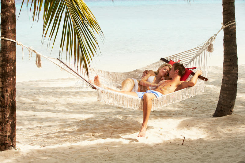 Romantic Couple Relaxing In Beach Hammock. Smiling stock images