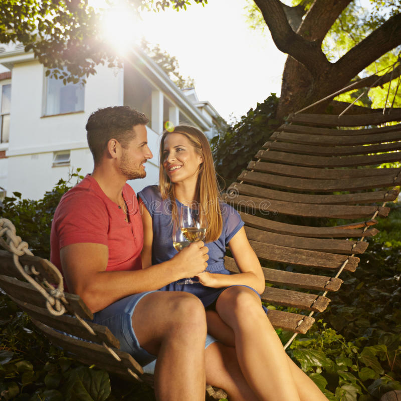 Romantic couple relaxing on hammock drinking wine. Romantic young couple toasting wine while sitting on a hammock in backyard. They are looking at each other stock photography