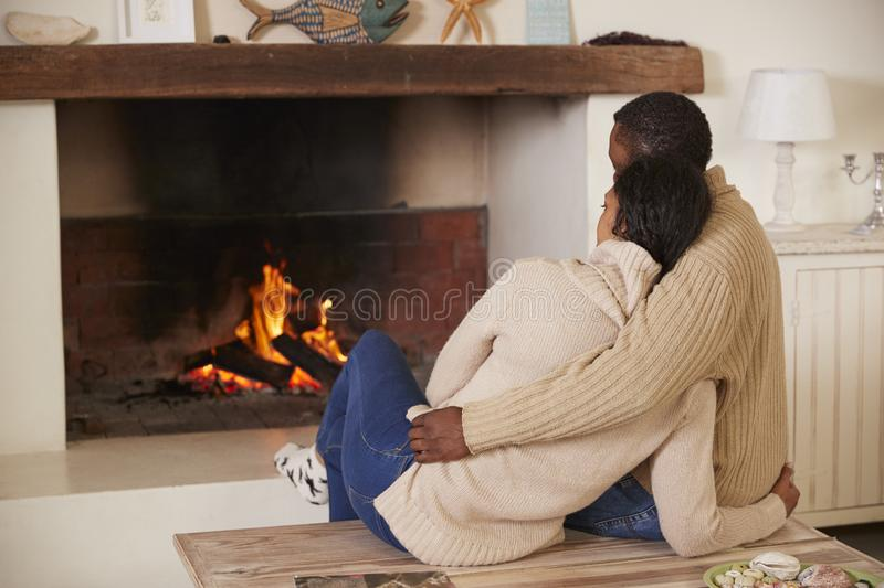 Romantic Couple Relaxing In Lounge Next To Open Fire royalty free stock photography