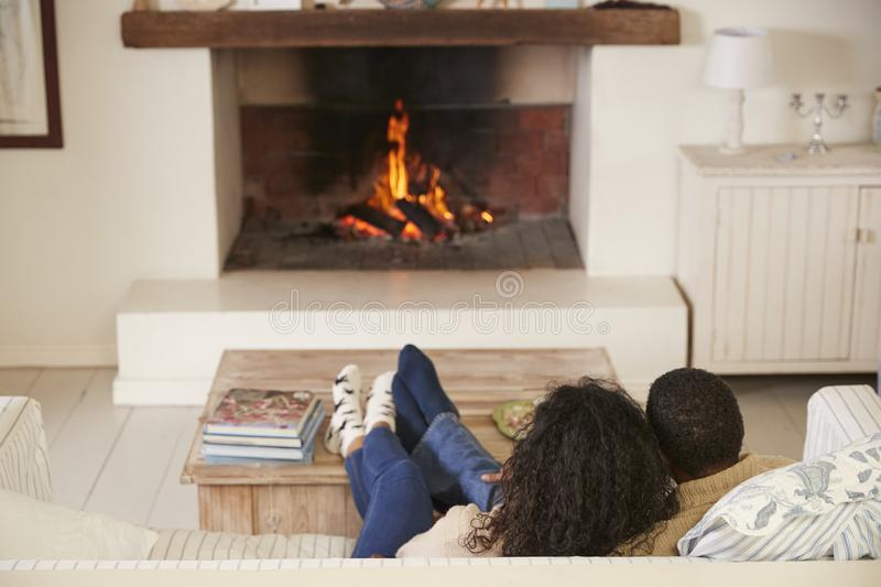Romantic Couple Relaxing In Lounge Next To Open Fire royalty free stock images