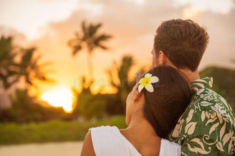 Romantic couple relaxing watching sunset on beach stroll view from back. Woman resting head on lover`s shoulder on honeymoon. Vacation travel in summer Hawaii royalty free stock image