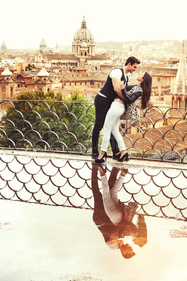 Romantic couple in Rome city, Italy. Loving relationship. Passion and love. A beautiful pair embrace on a terrace with a reflection in a puddle. Behind them the stock image
