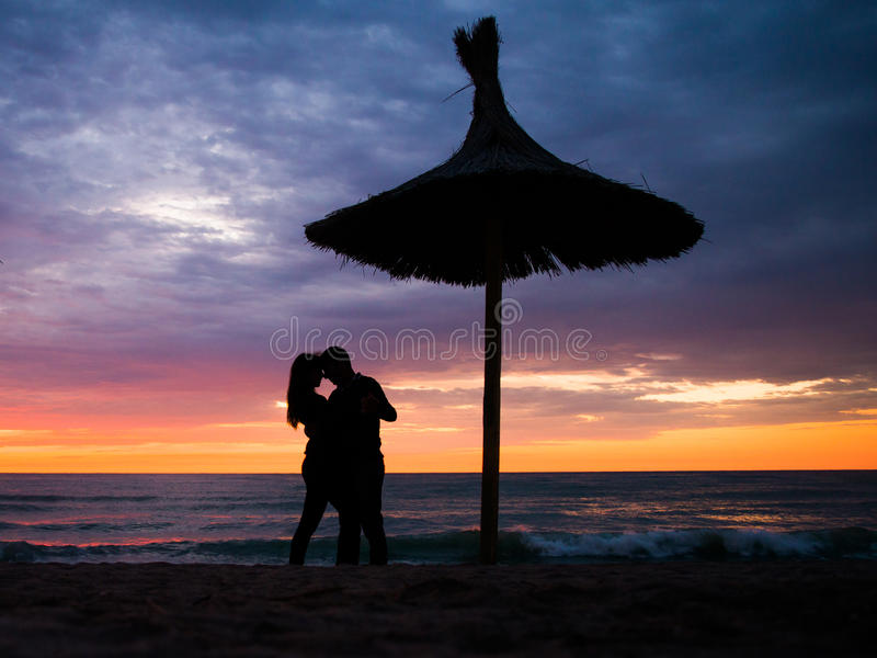Romantic couple by the sea. Romantic couple holding hands caring for each other at sunset. Valentines theme. Dramatic sunset. Colorful sky. Sea side romance stock images