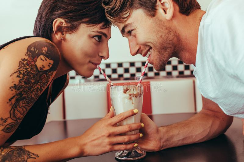 Romantic couple sharing milk shake using straws from the same gl. Close up of a happy couple sipping milk shake from a glass using straws while looking at each royalty free stock image