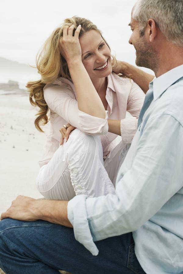 Romantic Couple Sitting On Beach stock photography