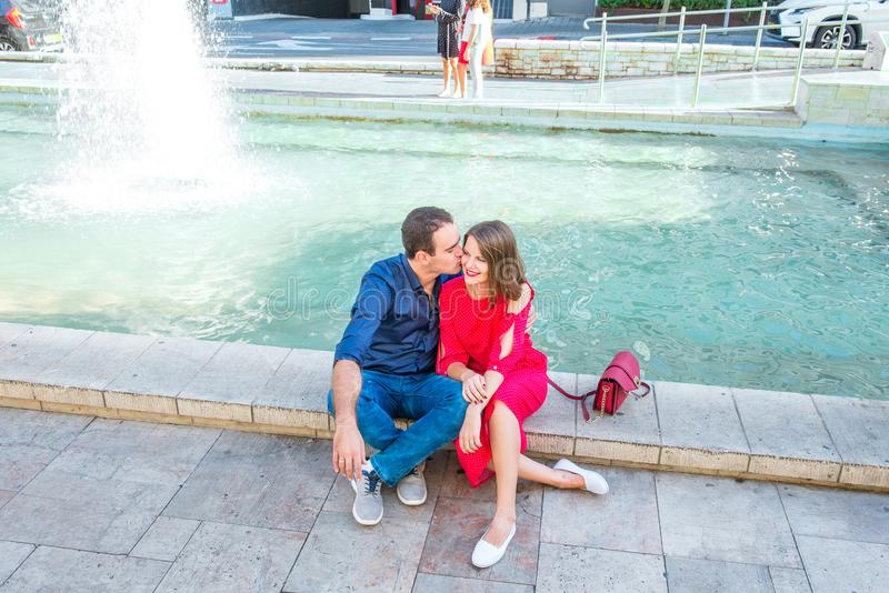 Romantic couple sitting on the bench near the city fountain and enjoying moments of happiness. Love, dating, romance. Lifestyle an stock images