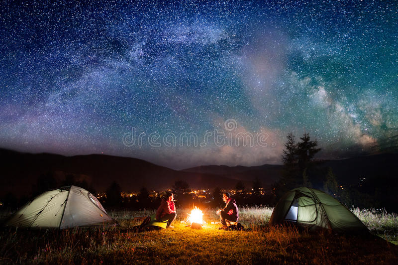 Romantic couple sitting at campfire near tents in the night. Romantic couple sitting at a campfire near tents in the night under incredibly beautiful starry sky royalty free stock photos