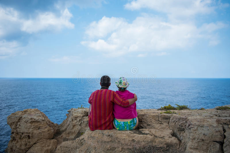 Romantic couple sitting on a cliff and admirig wonderful seascape stock image