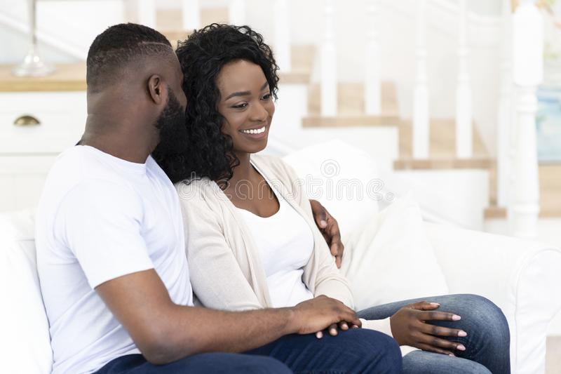 Romantic couple sitting on couch, embracing each other royalty free stock photography