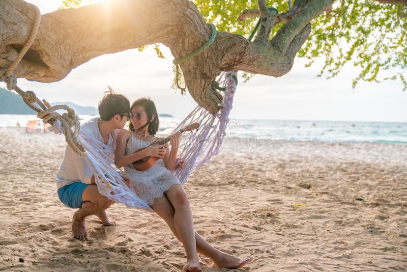 Romantic couple is sitting and kissing on sea beach on rope swing . Family vacation on honeymoon. Love and relationship.  stock image