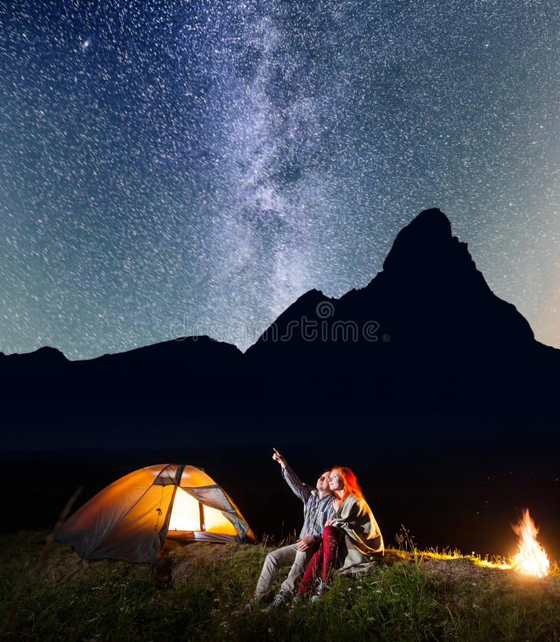 Download Romantic Couple Is Sitting Near The Glowing Tent And C&fire And Looking To The Stars & Romantic Couple Is Sitting Near The Glowing Tent And Campfire And ...
