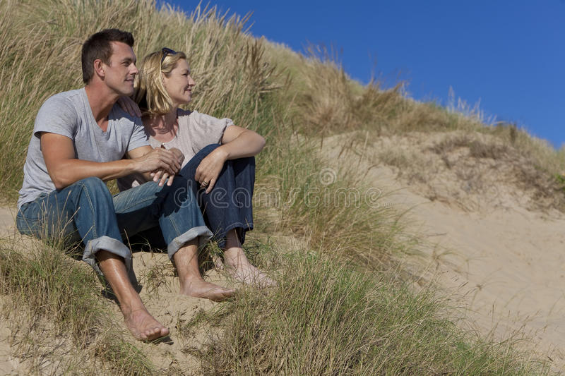 Romantic Couple Sitting Together On A Beach. A romantic young man and woman couple sitting together in the sand dunes of a sunny beach with a bright blue sky stock images