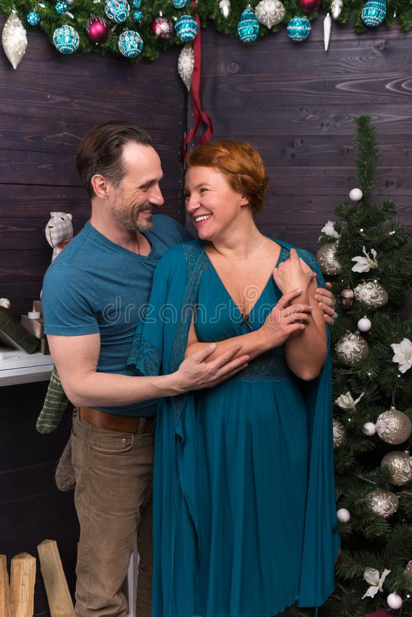 Romantic couple standing near the New Year tree and smiling. Cheerful relaxed romantic men hugging his beloved women and smiling while standing near the New Year stock image