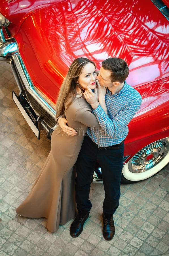 A romantic couple is standing by the red car. A man is hugging a woman. American classics. The guy and the girl next to the red ca. R. Californian dream concept royalty free stock photography