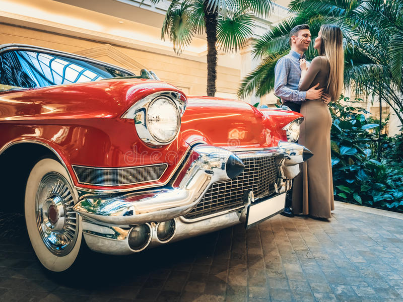 A romantic couple is standing by the red car. A man is hugging a woman. American classics. The guy and the girl next to the red ca royalty free stock images