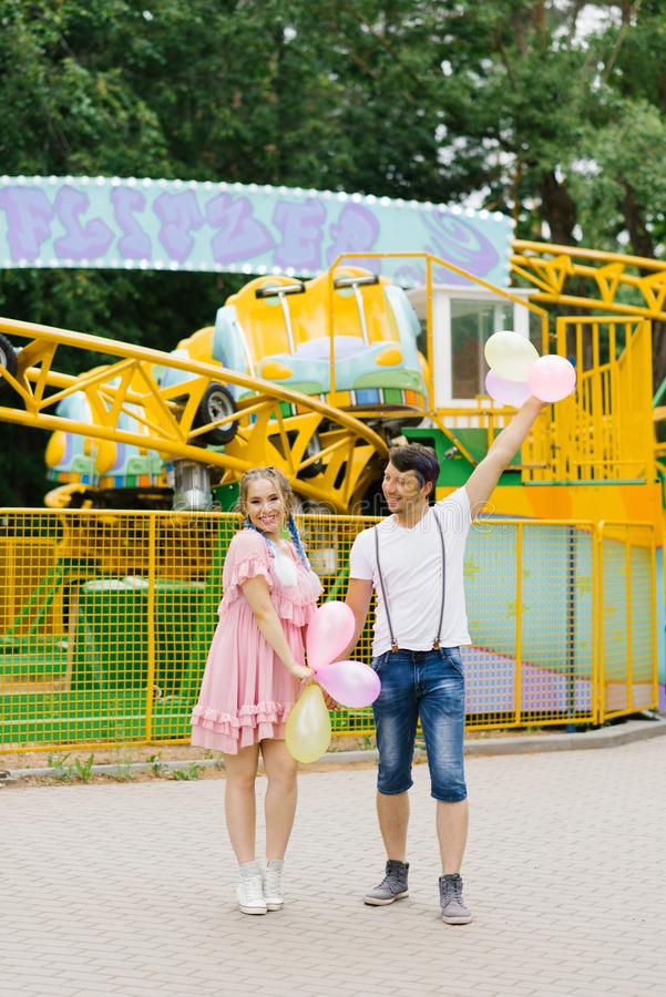 A romantic couple strolling through the amusement Park. The girl smiles, accepting a gift of balloons royalty free stock photography