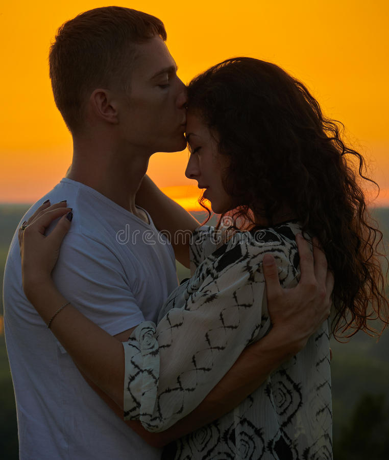 Romantic couple at sunset on outdoor, beautiful landscape and bright yellow sky, love tenderness concept, young adult people. Romantic couple at sunset on royalty free stock photo
