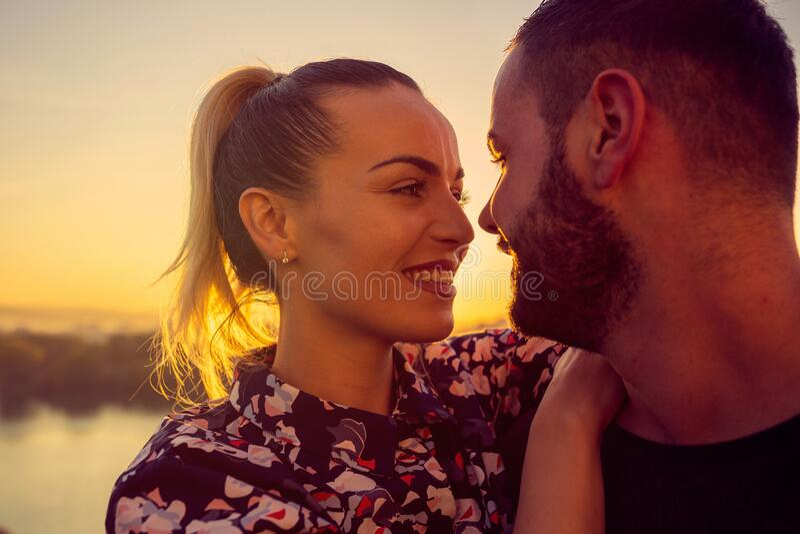 Romantic couple at sunset. Smiling man and woman is enjoying sunset stock photo