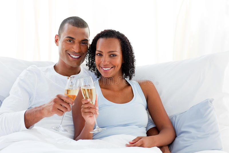 Romantic couple toasting with Champagne. Lying on their bed stock photos