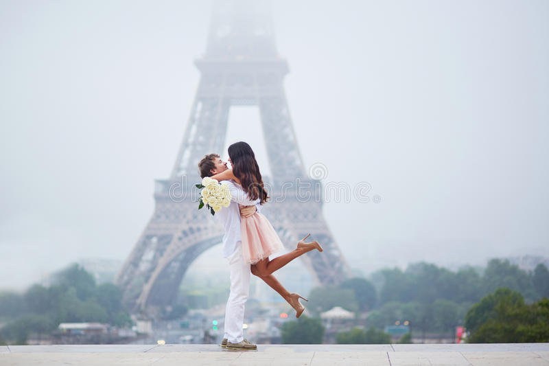 Romantic couple together in Paris. Beautiful romantic couple in love with bunch of white roses having fun near the Eiffel tower in Paris on a cloudy and foggy stock photography