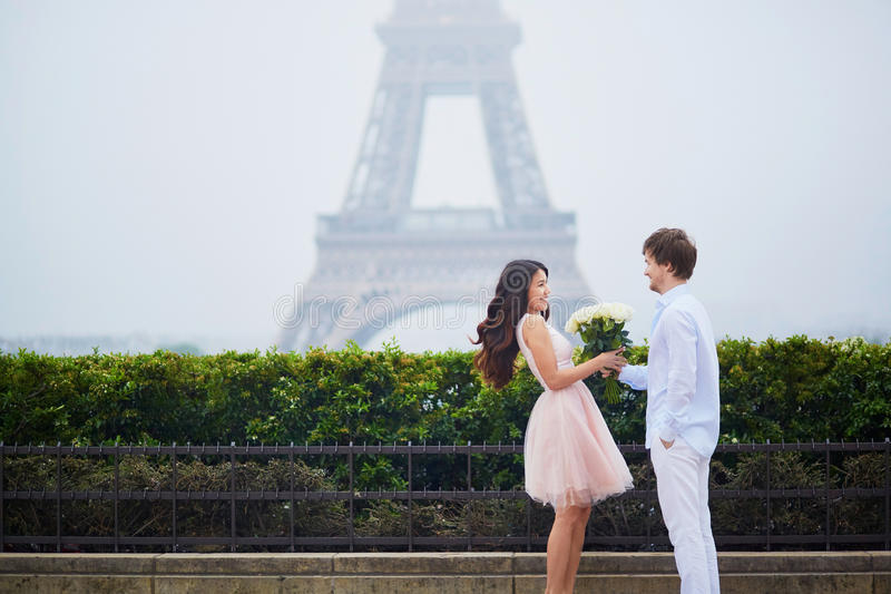 Romantic couple together in Paris. Beautiful romantic couple in love having a date near the Eiffel tower in Paris on a cloudy and foggy rainy day, men is stock photography