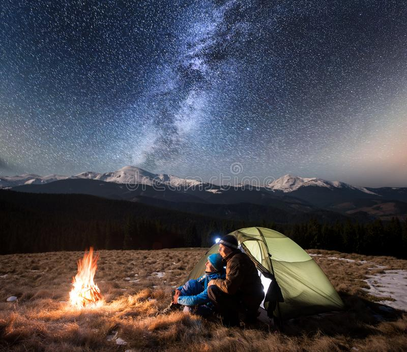 Couple tourists enjoying in the camping at night, having a rest under beautiful night sky full of stars and milky way. Romantic couple tourists enjoying in the royalty free stock photography