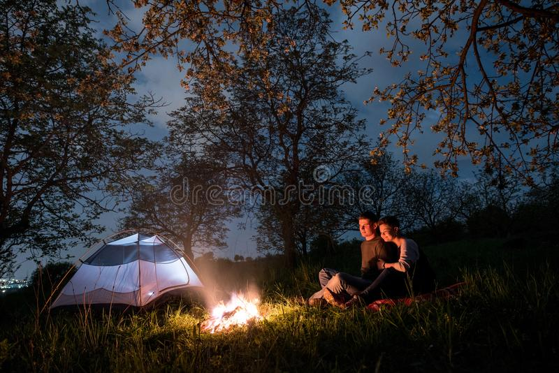 Couple tourists sitting at a campfire near tent, hugging each other under trees and night sky. Night camping royalty free stock photos