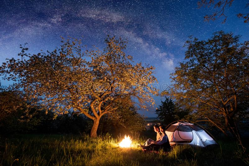 Romantic couple tourists sitting at a campfire near tent under trees and beautiful night sky full of stars and milky way. Night camping. Long exprose royalty free stock images