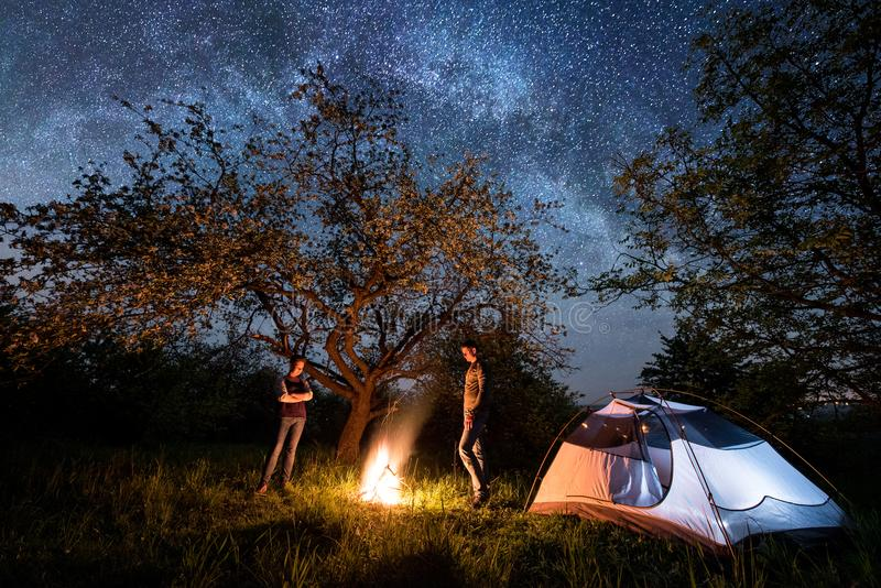 Romantic couple tourists standing at a campfire near tent under trees and night sky full of stars and milky way. Romantic couple tourists standing at a campfire stock photos