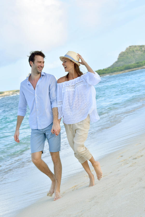 Romantic couple walking on the beach at sunset royalty free stock image