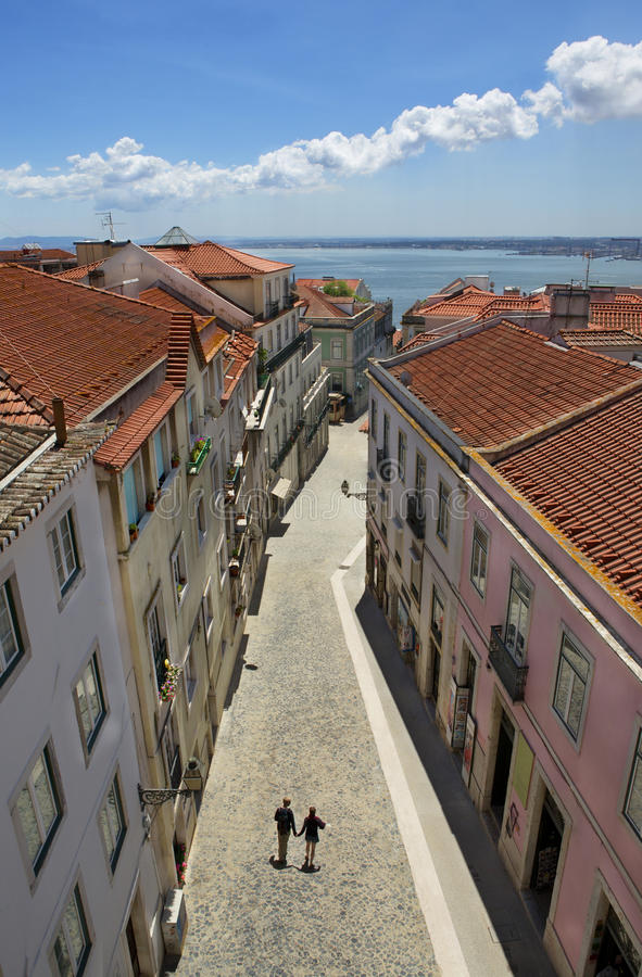 Romantic couple walking on the narrow street of old Europe. Lisbon, capital of Portugal royalty free stock photography