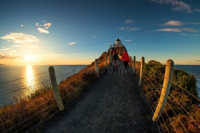 Romantic couple walking towards lighthouse at Nugget Point, Dunedin, New Zealand royalty free stock image