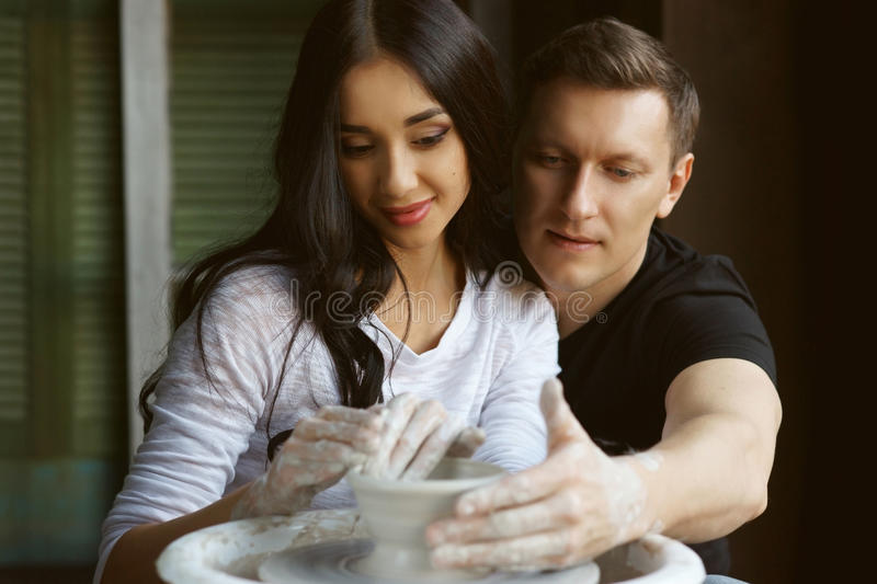 Romantic couple working on potter wheel. Pottery couple making clay pot on potter`s wheel. Handsome men and beautiful pretty women in love working together stock photo