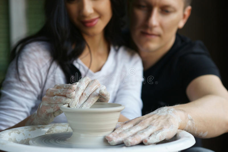 Romantic couple working on potter wheel. Romatic couple working on potter wheel and making or sculpting clay pot. Focus on hands stock images
