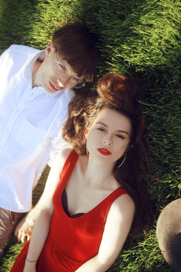 Romantic couple of young people lying on grass in park. Happy Couple Relaxing on Green Grass. Park. A girl in a beautiful dress royalty free stock image