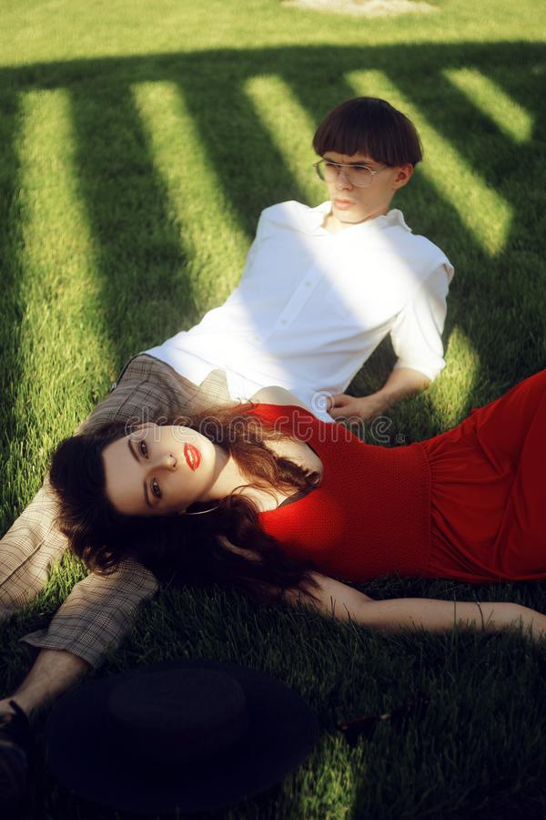 Romantic couple of young people lying on grass in park. Happy Couple Relaxing on Green Grass. Park. A girl in a beautiful dress stock photography