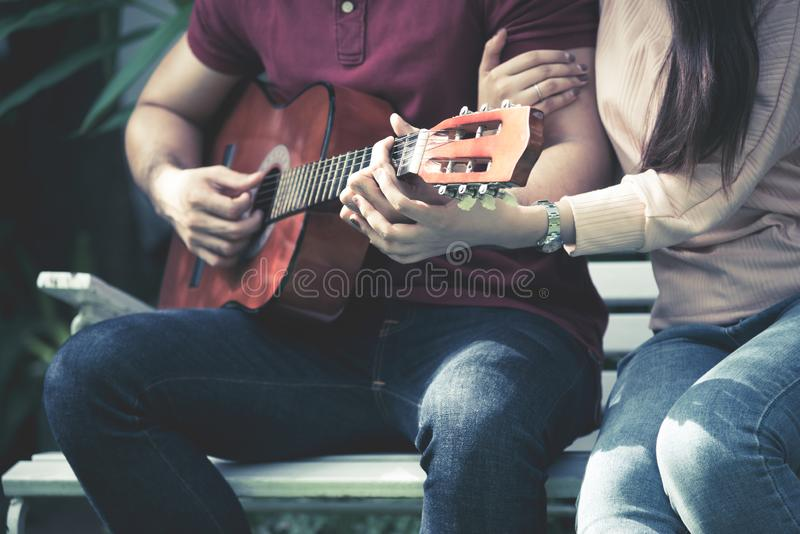 Romantic couples playing guitar together stock photography