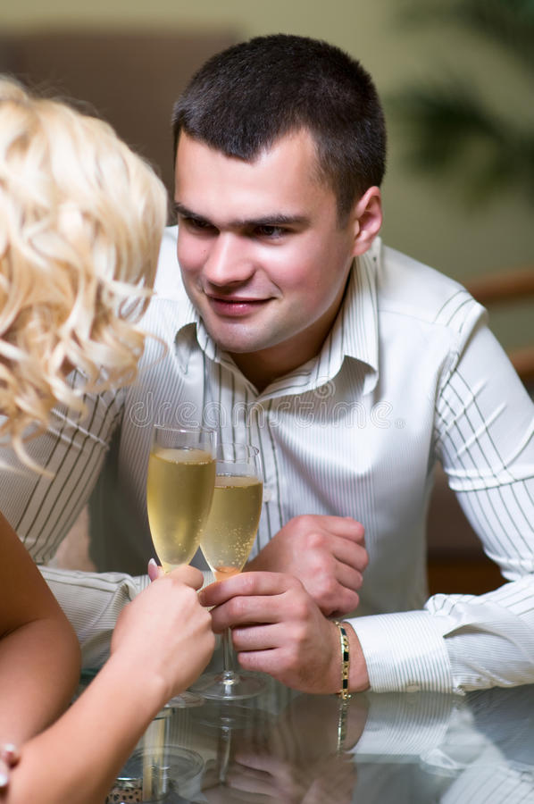 Romantic date. Young couple sharing champagne glasses in a restaurant, on romantic date. Focus on male stock photography