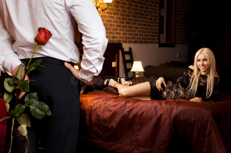 Romantic date. Romantic evening date in hotel room, guy with girl on bed stock image