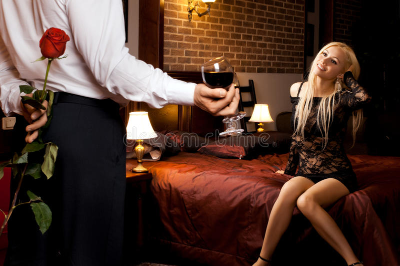 Romantic date. Romantic evening date in hotel room, guy with girl on bed stock photo