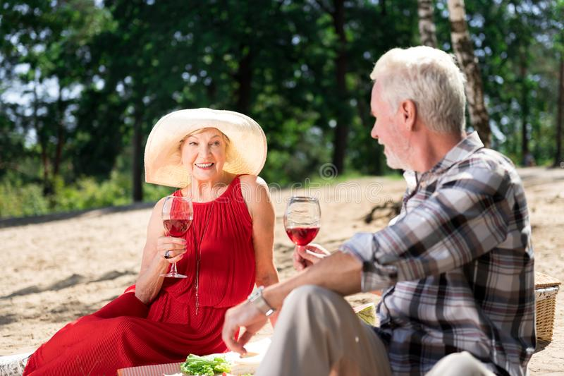 Happy elderly woman looking at husband having romantic date royalty free stock photography