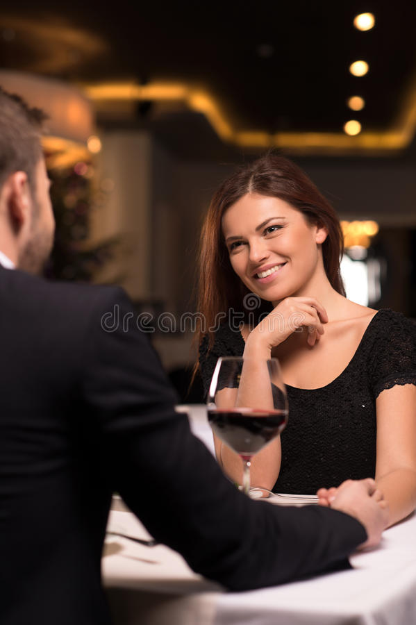 Romantic date at the restaurant. Beautiful young couple talking to each other and smiling while spending time at the restaurant royalty free stock image