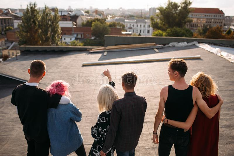 Romantic date rooftop diverse couples love hangout. Romantic relationship. Teenage dating. Back view of diverse youn couples in love hanging out together on a royalty free stock photo