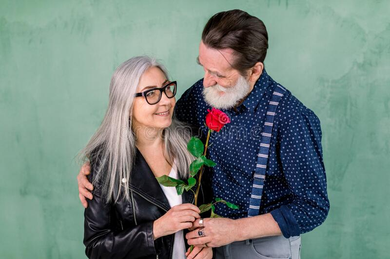 Romantic date, senior couple with a red rose in love. Senior handsome bearded man offering a rose to his partner. Charming gray haired lady, standing together stock photos