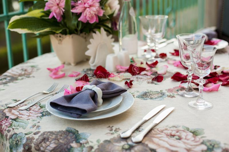 Romantic decor of the festive table in the restaurant with candles, flowers, rose petals stock photo