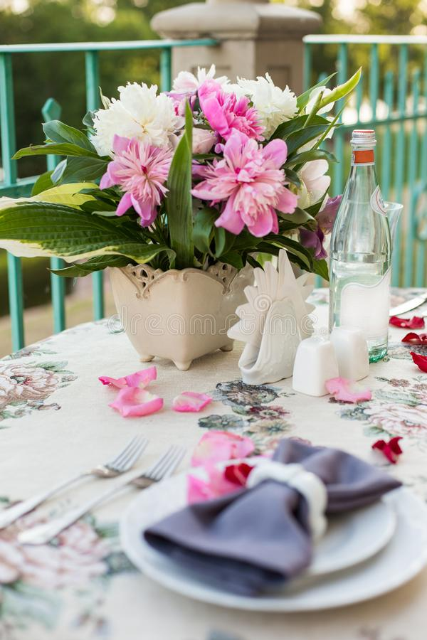 Romantic decor of the festive table in the restaurant with candles, flowers, rose petals royalty free stock image