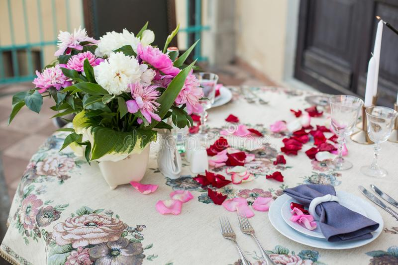 Romantic decor of the festive table in the restaurant with candles, flowers, rose petals royalty free stock photography