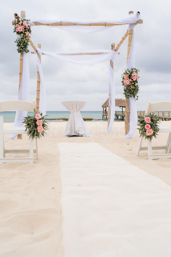Romantic decoration of a pavilion of a beach wedding on the beach with sea in the background and cloudy sky royalty free stock images